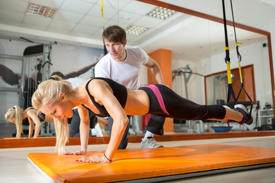 girl doing pushups with resistance band in the presence of a personal trainer