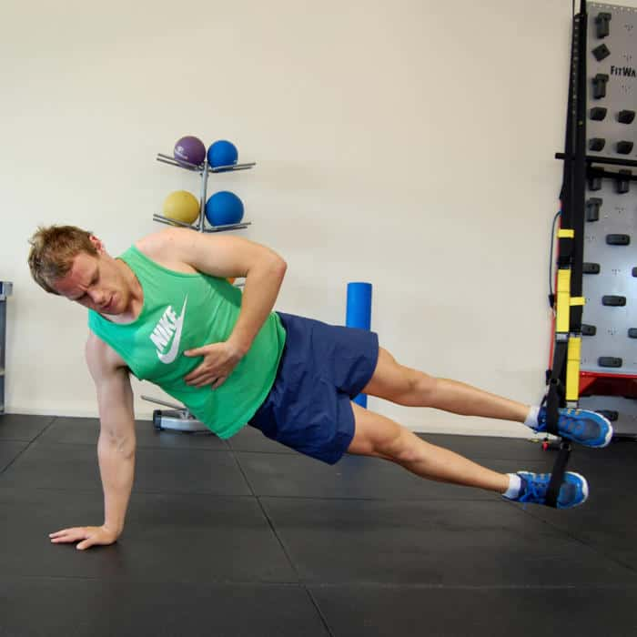 Man performing the TRX side plank on hands