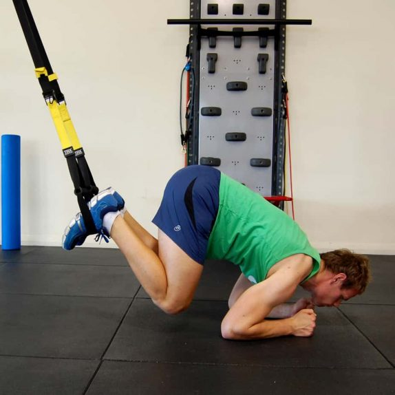 Man performing the TRX body saw with crunch
