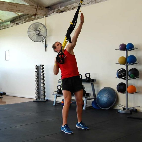 Man performing a TRX single arm reach