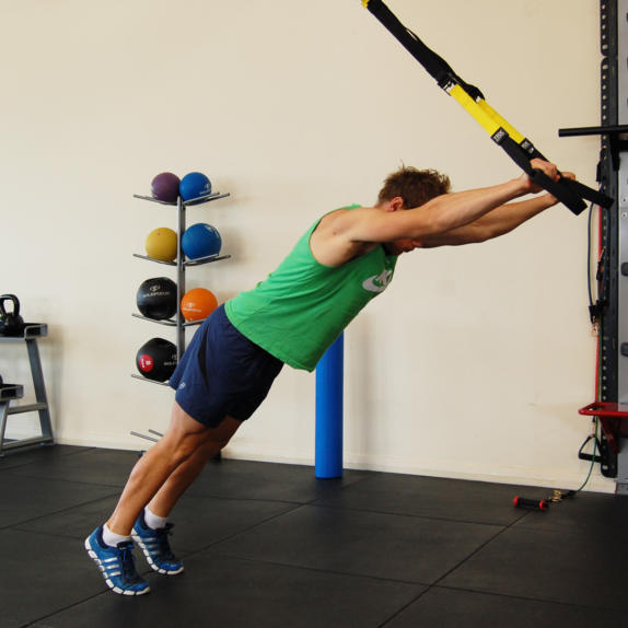 Man performing the TRX standing roll out